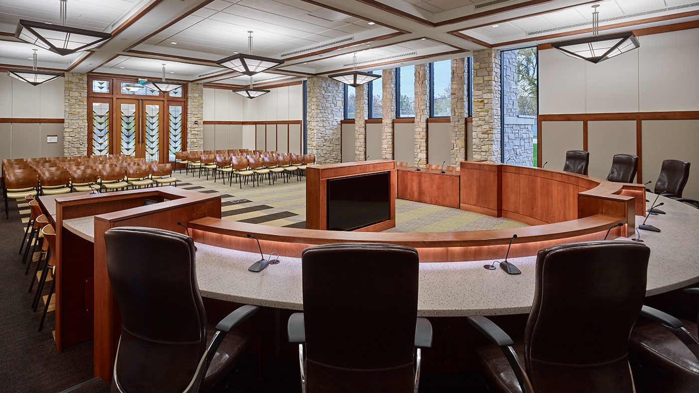 The new council chambers interiors feature stone pier accents, a raised wood dais, coffered ceilings, and prairie-inspired stained glass entry doors.