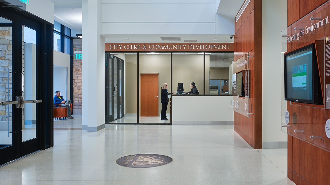 The single public entry in this combined facility features a dramatic, light-filled two-story lobby with prairie-style inspired pendant light fixtures, wood paneled signage and display walls, and seating areas with views out to the civic lawn.