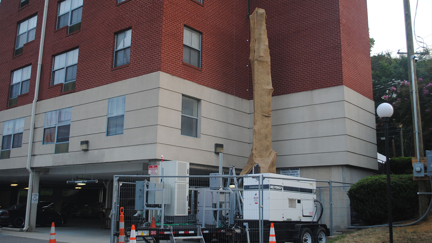 Antennas were serviced by a ground-level mobile trailer connected to the rooftop equipment through a partially erected tower and cables.